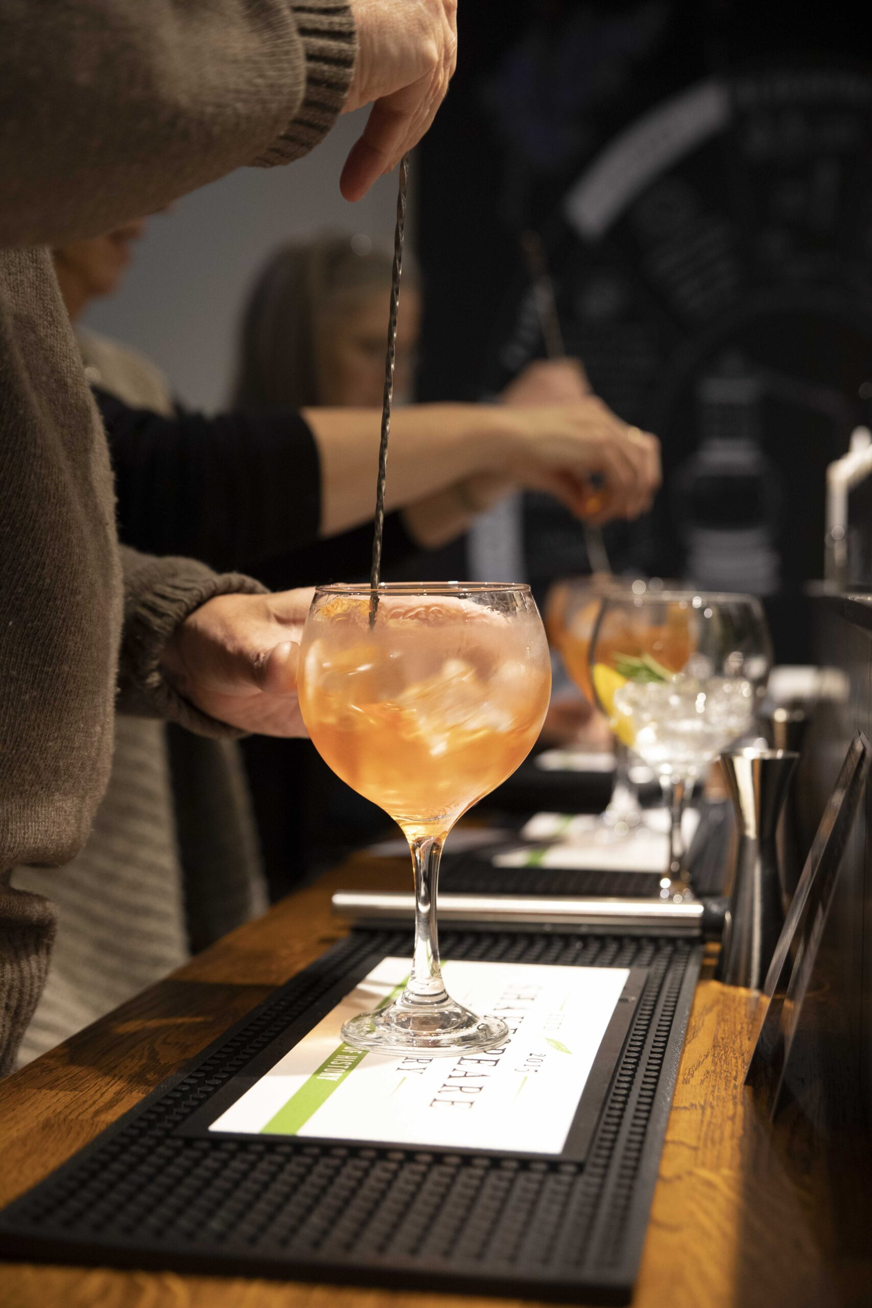 people stirring their cocktails at masterclass