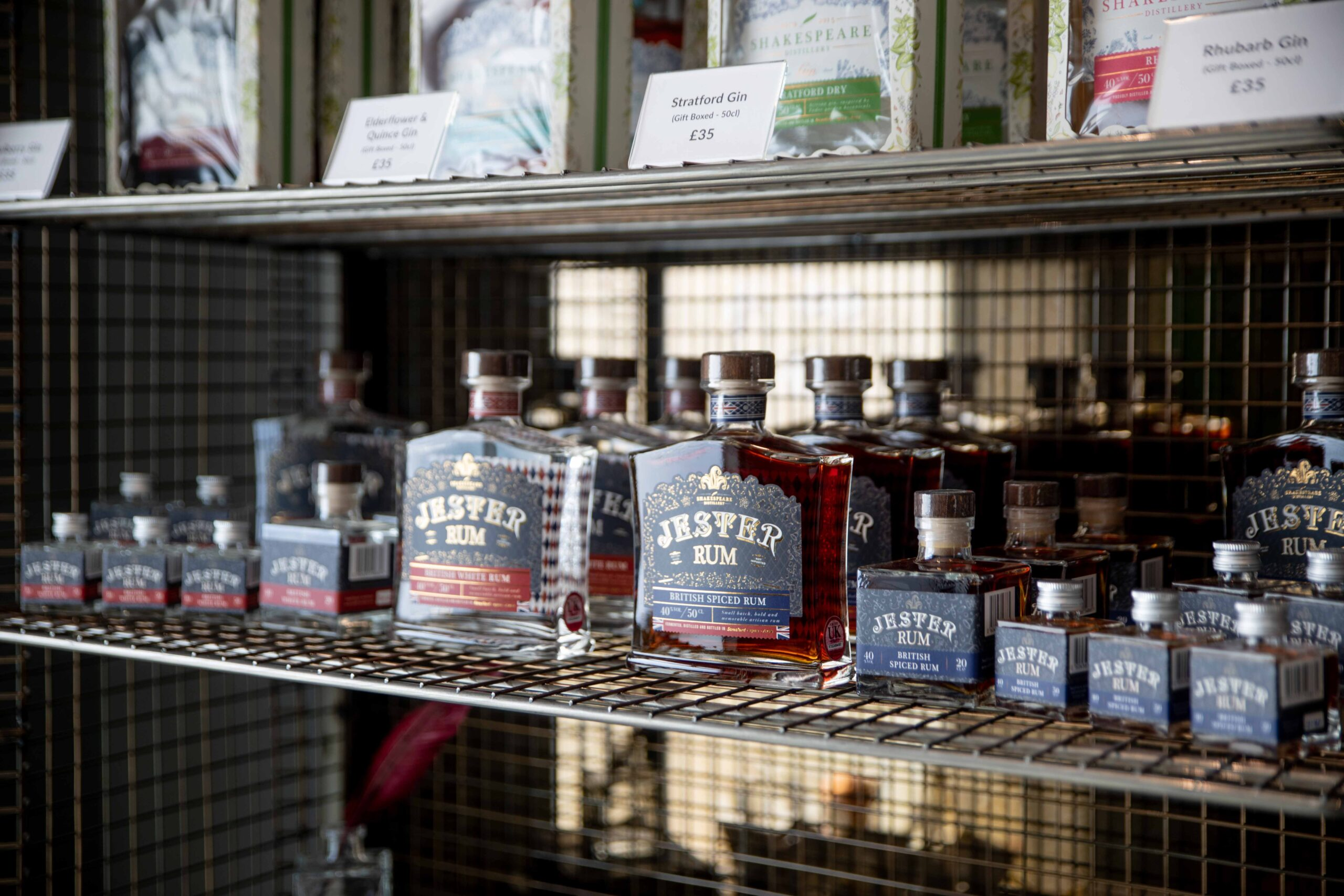 a shelf with many bottles of jester rum